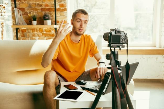 Jonge blanke mannelijke blogger met professionele camera opname videoreview van gadgets thuis. bloggen, videoblog, vloggen. man die vlog of livestream maakt over foto of technische nieuwigheid.