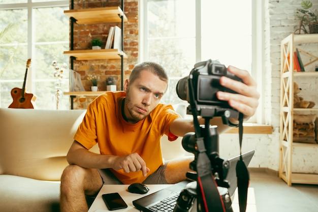 Jonge blanke mannelijke blogger met professionele camera opname videoreview van gadgets thuis.