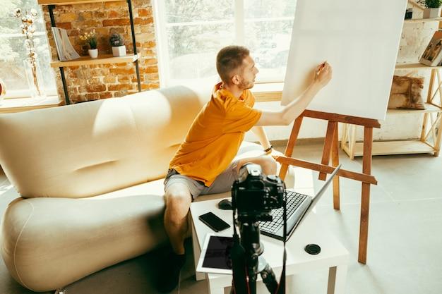 Jonge blanke mannelijke blogger met professionele camera opname videoreview van gadgets thuis