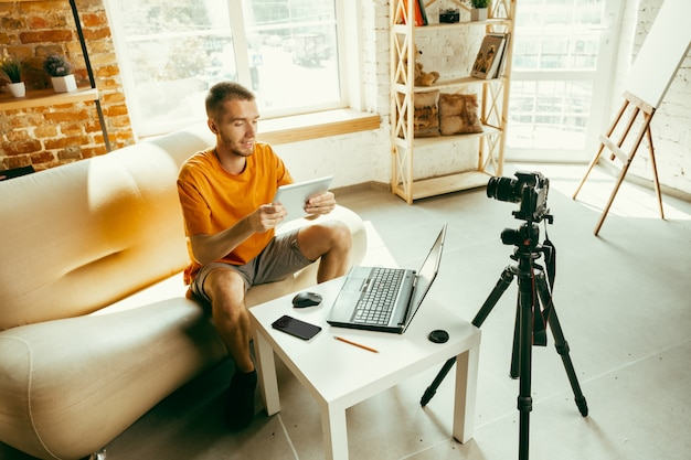Jonge blanke mannelijke blogger met professionele camera opname videoreview van tablet thuis