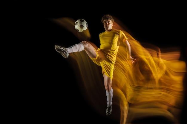 Jonge blanke mannelijke voetbal of voetballer schoppen bal voor het doel in gemengd licht op donkere muur concept van gezonde levensstijl professionele sport hobby