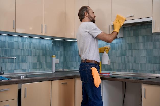 Jonge blanke mannelijke werknemer die keukenmeubels schoonmaakt