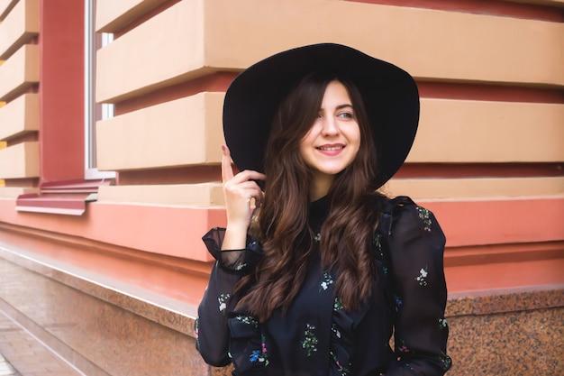 Jonge blanke meisje in een zwarte hoed op een stadswandeling.