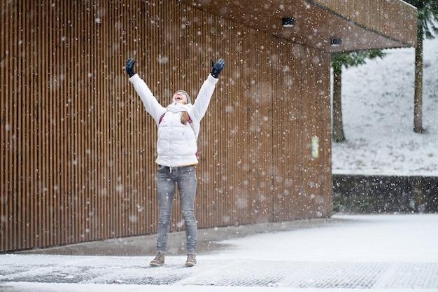 Jonge blanke meisje lachen vangen sneeuwvlokken op haar toungue