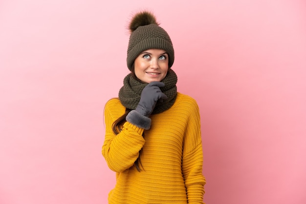 Jonge blanke meisje met winter hoed geïsoleerd op roze achtergrond en opzoeken background