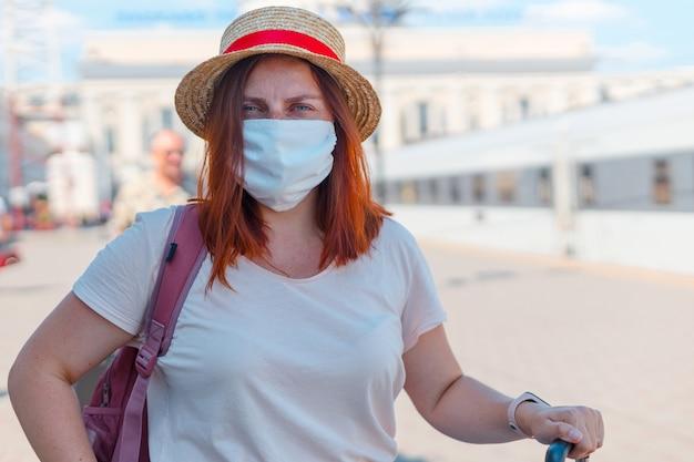 Jonge blanke meisje reiziger met een rugzak en in een beschermend masker tijdens het wachten op het openbaar vervoer op het station.