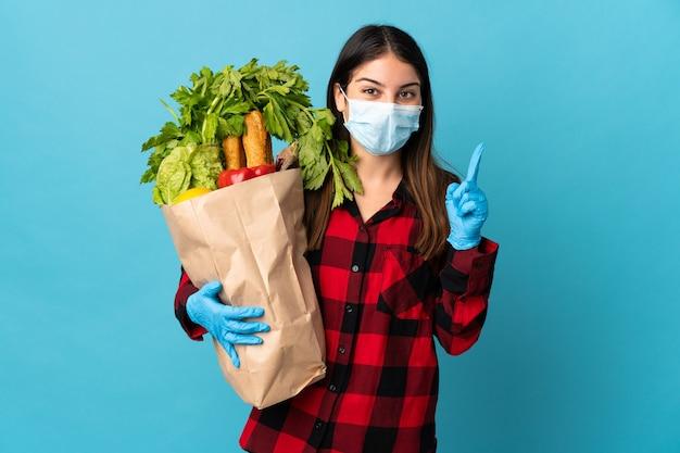 Jonge blanke met groenten en masker geïsoleerd op blauw met een geweldig idee