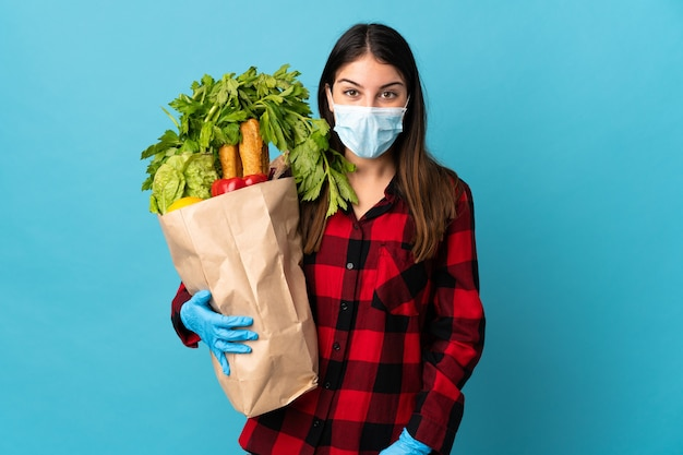 Jonge blanke met groenten en masker geïsoleerd op blauw met verbazing en geschokt gelaatsuitdrukking