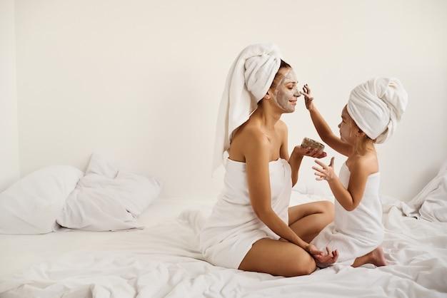Jonge blanke moeder en dochtertje met ingepakt haar in witte badhanddoeken passen een kleimasker toe op de moedergezichten