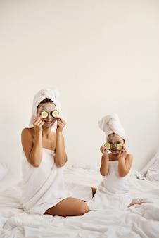 Jonge blanke moeder en haar dochtertje met ingepakt haar in witte badhanddoeken hebben plezier en brengen stukjes komkommer aan op hun ogen.