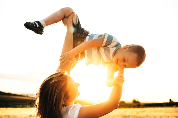 Jonge blanke moeder speelt met zijn zoon tegen zonsondergang lachen in een tarweveld.