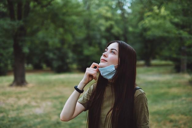 Jonge blanke mooie vrouw verwijdert een medisch beschermend masker op de natuur, schone frisse lucht inademen.