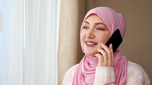 Jonge blanke moslimvrouw kijkt uit het raam praten aan de telefoon.