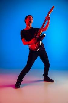 Jonge blanke muzikant die gitaar speelt in neonlicht op blauwe achtergrond, geïnspireerd