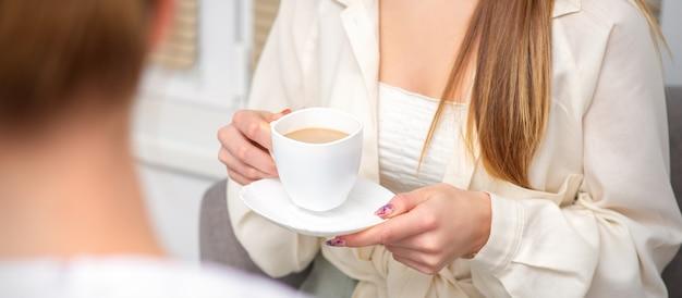 Jonge blanke onherkenbare vrouw met een kop warme drank op een doktersafspraak in het ziekenhuiskantoor