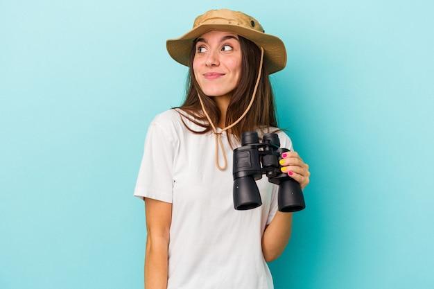 Jonge blanke ontdekkingsreiziger vrouw met verrekijker geïsoleerd op blauwe achtergrond dromen van het bereiken van doelen en doeleinden
