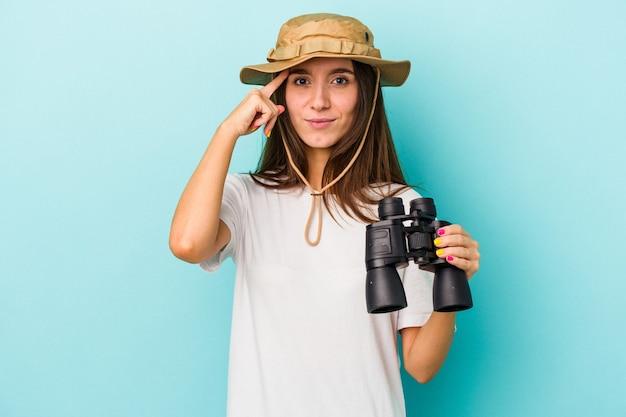 Jonge blanke ontdekkingsreiziger vrouw met verrekijker geïsoleerd op blauwe achtergrond wijzende tempel met vinger, denken, gericht op een taak.