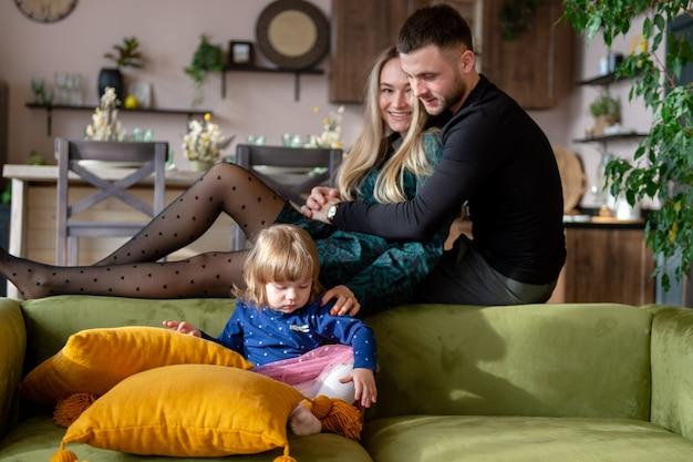 Jonge blanke ouders met plezier met hun dochtertje in interieur studio.