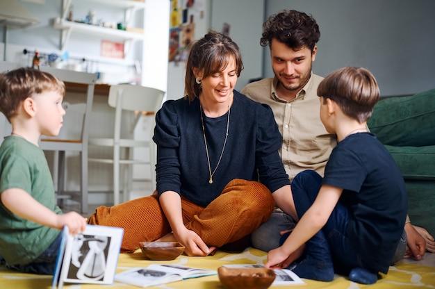 Jonge blanke ouders tijd thuis doorbrengen met zonen en het lezen van boeken op de vloer. spelen met voorschoolse kinderen en gelukkige familie. home onderwijs concept