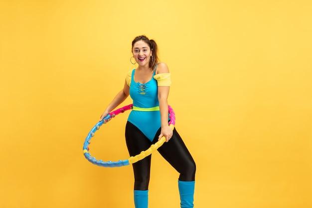 Jonge blanke plus size vrouwelijk model training op geel training