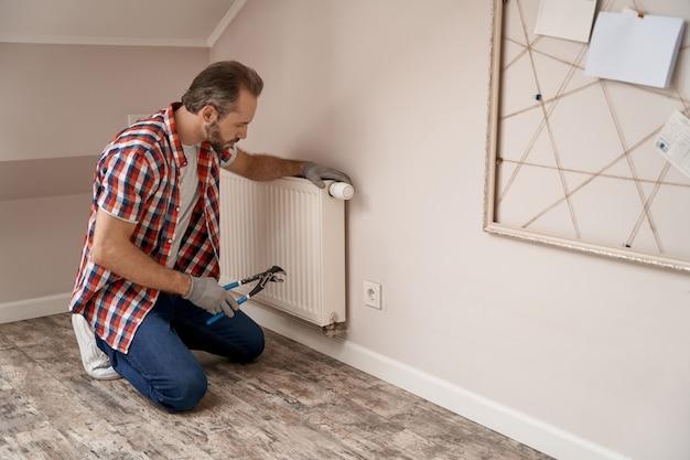 Jonge blanke reparateur zittend op knieën in de buurt van radiator