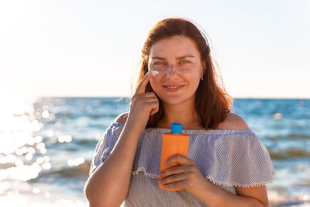 Jonge blanke roodharige meisje glimlachend in een zomerjurk houdt een plastic fles mos met zonnebrandcrème en smeert het op haar gezicht.