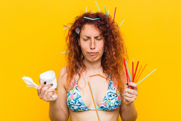 Jonge blanke roodharige vrouw boos op het misbruik van plastic