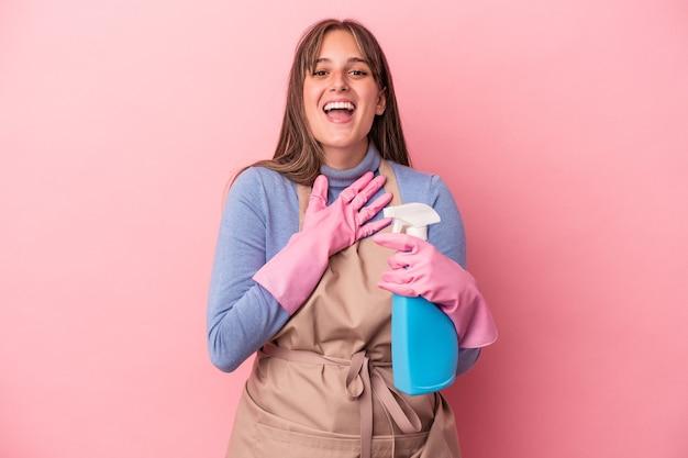 Jonge blanke schonere vrouw met spray geïsoleerd op roze achtergrond lacht hardop terwijl ze de hand op de borst houdt.