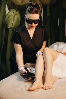 Jonge blanke spa-medewerker heeft een epileersessie met moderne apparaten terwijl hij een beschermende bril draagt