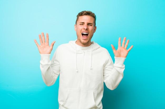 Jonge blanke sport man viert een overwinning of succes, hij is verrast en geschokt.