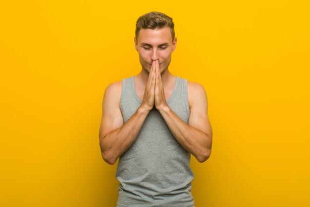 Jonge blanke sportman die hand in hand bidt in de buurt van de mond, voelt zich zelfverzekerd.