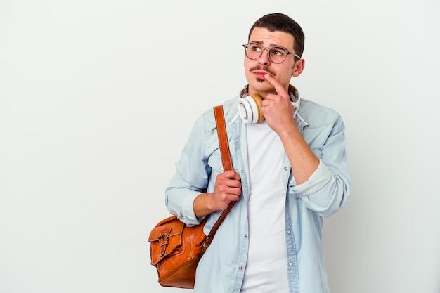 Jonge blanke student man luisteren naar muziek op wit zijwaarts kijken met twijfelachtige en sceptische uitdrukking.