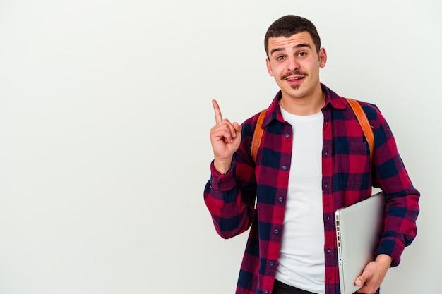 Jonge blanke student man met een laptop geïsoleerd op wit glimlachend vrolijk wijzend met wijsvinger weg.