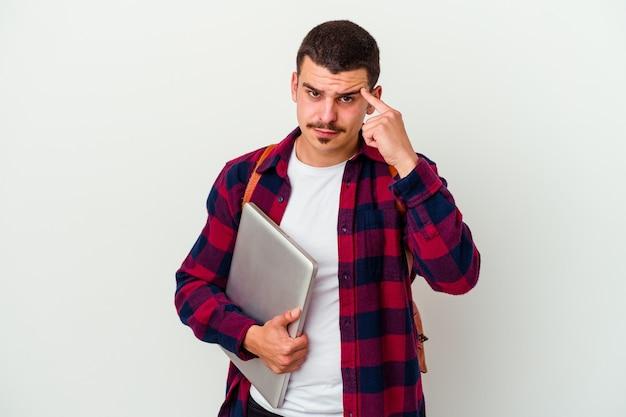 Jonge blanke student man met een laptop geïsoleerd op wit wijzende tempel met vinger, denken, gericht op een taak.