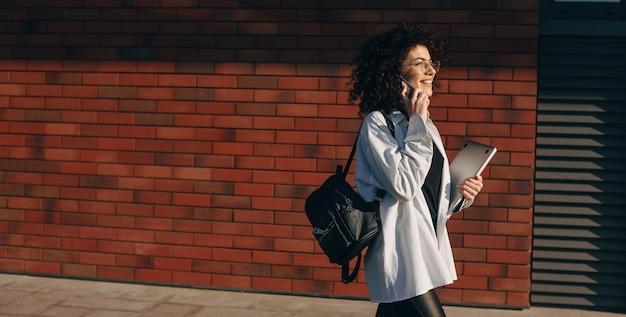 Jonge blanke student met krullend haar praat aan de telefoon tijdens het wandelen met een tas en laptop