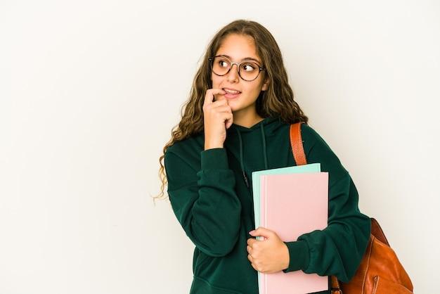 Jonge blanke student vrouw geïsoleerd ontspannen denken aan iets kijken naar een kopie ruimte.