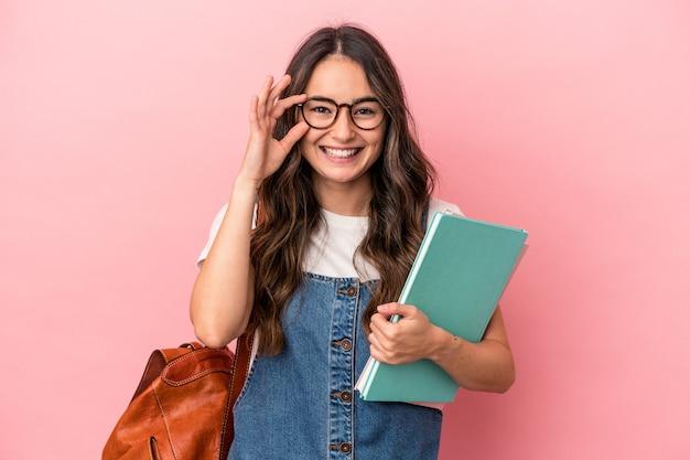 Jonge blanke student vrouw geïsoleerd op roze achtergrond opgewonden houden ok gebaar op oog.