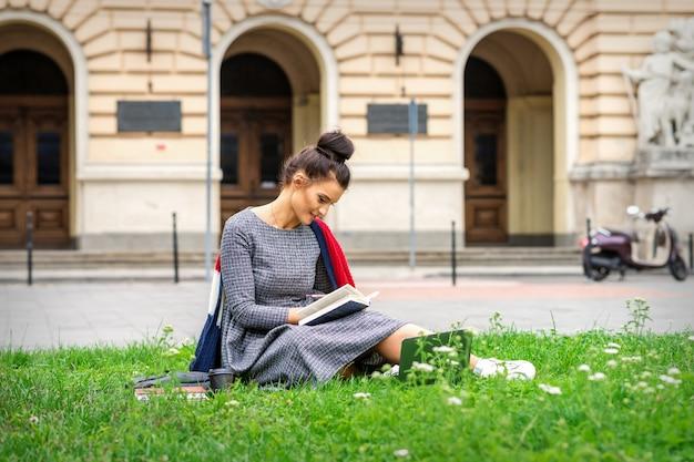 Jonge blanke student vrouw lezen van het boek zittend op het gras in de buurt van de universiteit op straat