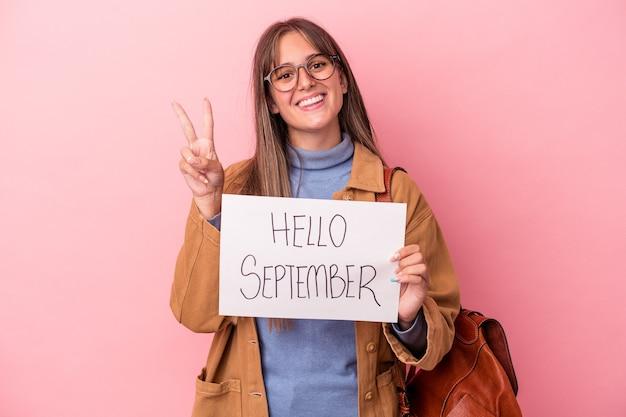 Jonge blanke student vrouw met hallo september plakkaat geïsoleerd op roze achtergrond met nummer twee met vingers.