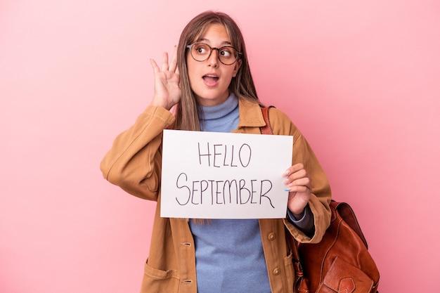 Jonge blanke student vrouw met hallo september plakkaat geïsoleerd op roze achtergrond probeert te luisteren naar een roddel.