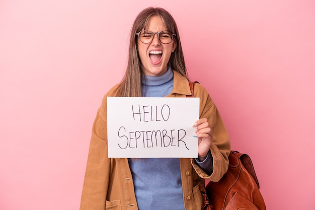 Jonge blanke student vrouw met hallo september plakkaat geïsoleerd op roze achtergrond schreeuwen erg boos en agressief.
