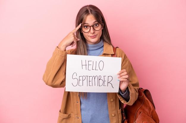 Jonge blanke student vrouw met hallo september plakkaat geïsoleerd op roze achtergrond wijzende tempel met vinger, denken, gericht op een taak.