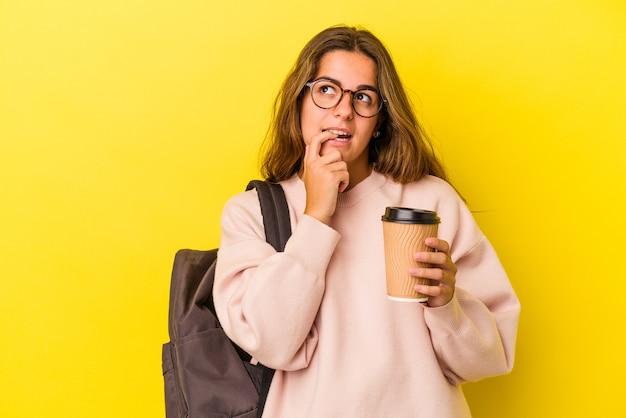 Jonge blanke student vrouw met koffie geïsoleerd op gele achtergrond ontspannen denken over iets kijken naar een kopie ruimte.