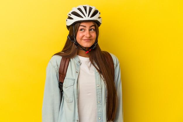 Jonge blanke studente die een fietshelm draagt die op gele achtergrond wordt geïsoleerd en droomt van het bereiken van doelen en doeleinden
