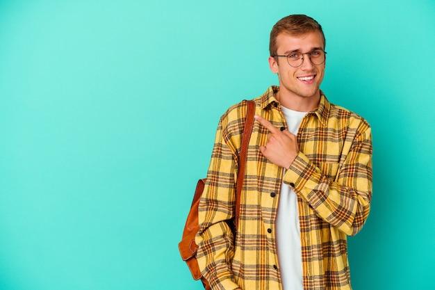 Jonge blanke studentenmens die op blauwe muur wordt geïsoleerd die en opzij glimlacht richt, die iets op lege ruimte toont.