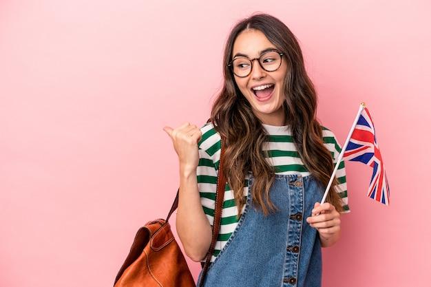 Jonge blanke studentenvrouw die engels studeert geïsoleerd op roze achtergrond wijst met duimvinger weg, lachend en zorgeloos.