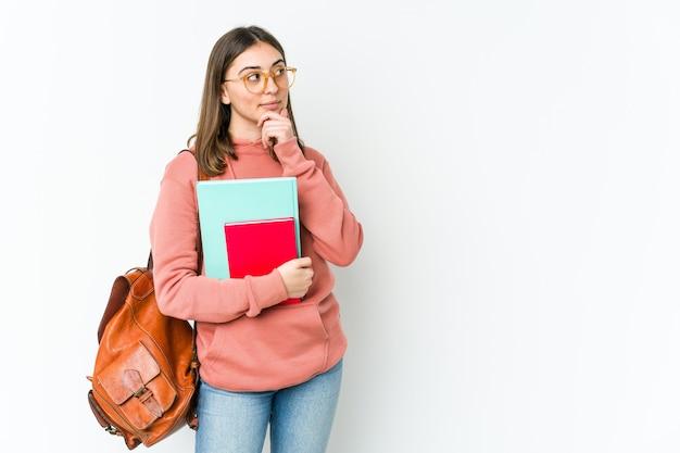 Jonge blanke studentenvrouw die op witte muur wordt geïsoleerd die zijwaarts met twijfelachtige en sceptische uitdrukking kijkt.