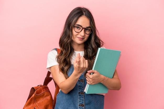 Jonge blanke studentenvrouw geïsoleerd op een roze achtergrond die met de vinger naar je wijst alsof uitnodigend dichterbij komt.