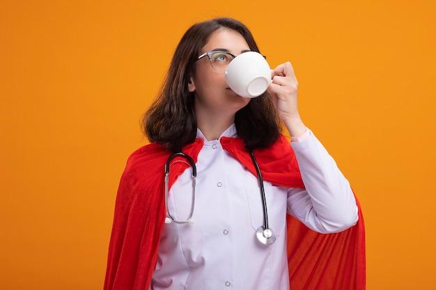 Jonge blanke superheldenmeisje met doktersuniform en stethoscoop met een bril die op zoek is naar een kopje thee