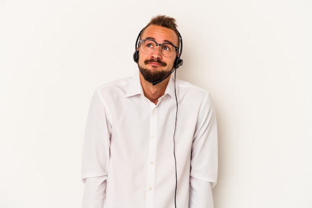 Jonge blanke telemarketeer man met tatoeages geïsoleerd op een witte achtergrond dromen van het bereiken van doelen en doeleinden